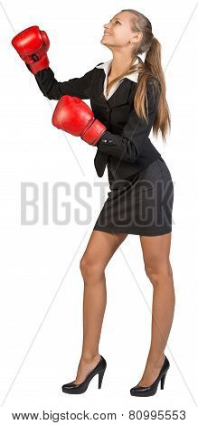 Businesswoman wearing boxing gloves, looking ahead and upwards, smiling