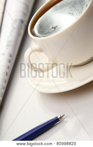 A white cup of cappuccino and a blue pen on paper table numbers