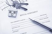 stock photo of rental agreement  - Rental agreement document with keys and pencil - JPG