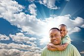 foto of pre-adolescent child  - Happy African American Man with Child Over Blue Sky Clouds and Sun Rays - JPG
