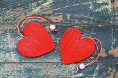 image of two hearts  - Two red wooden hearts on rustic wooden surface - JPG