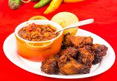 stock photo of jalapeno  - Serving of spicy wings in Honey BBQ Sauce on plate with bowl of homemade chili and Jalapeno cornbread - JPG