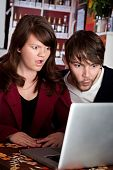 picture of smut  - Woman and man staring with shock at laptop computer - JPG