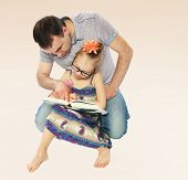 stock photo of child development  - Dad and daughter reading a book - JPG