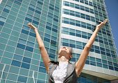 stock photo of open arms  - Happy businesswoman on modern business center background selective focus - JPG