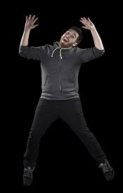 stock photo of wacky  - Full Length Shot of Happy Young Man in Casual Attire Doing Wacky Pose While Looking at the Camera on Black Background - JPG