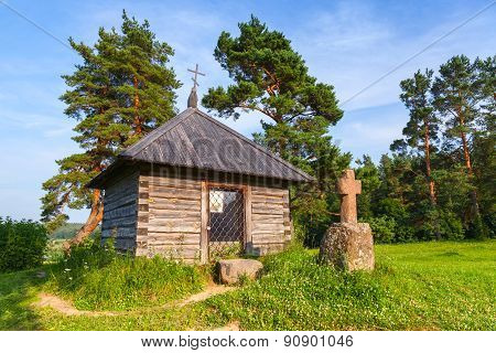 Ancient Wooden Orthodox Chapel And A Stone Cross