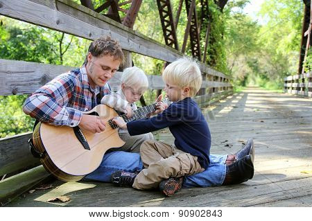 Father And Two Children Playing Guitar Outside At Park