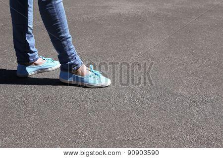 Female feet on gray asphalt background