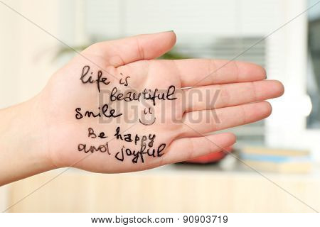 Female hand with written message in room