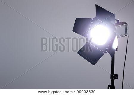 Photo studio with lighting equipment on grey wall background
