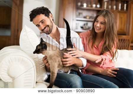 Portrait of an happy couple playing with their cat on the couch. Shallow depth of field, focus on the man