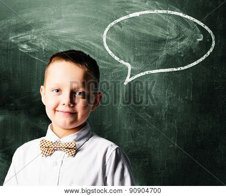school boy is standing with blackboard behind him
