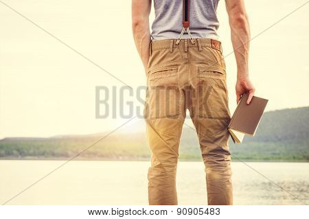 Young Man standing with book outdoor with scandinavian lake on background Education and Lifestyle