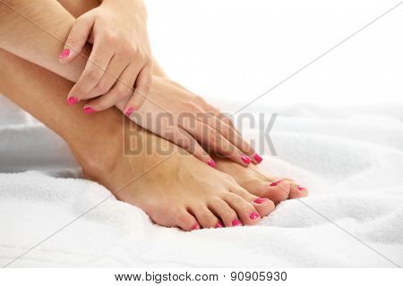 Beautiful female legs on towel, isolated on white background