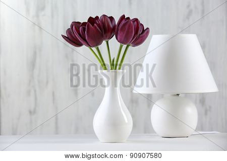 Beautiful violet tulip in vase with lamp on gray background