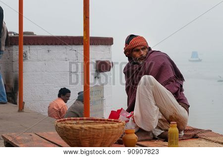 Indian Man Sits On The Ghat Near Sacred River Ganges In Varanasi