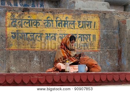 Indian Man Sits On The Steps Of Ghat Near Sacred River Ganges In Varanasi