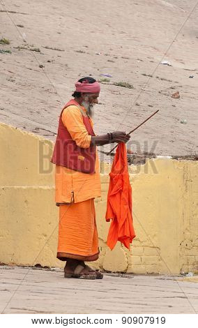 Indian Sadhu On Ghat Near Sacred River Ganges In Varanasi