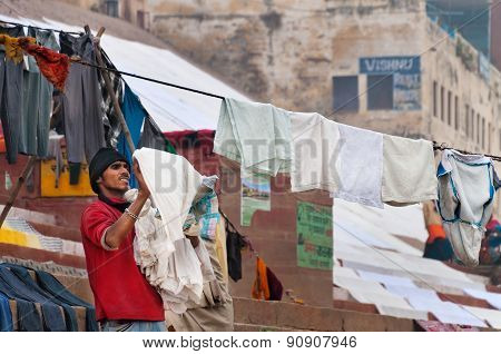 Indian Man Hang The Wash On Clothesline On Ghat Near Sacred River Ganges In Varanasi