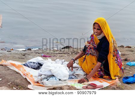 Indian Woman Washes Clothes On Ghat Near Sacred River Ganges In Varanasi