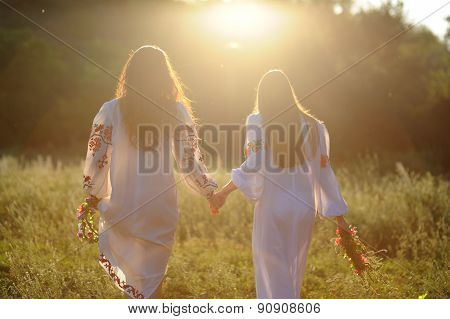 Two Girls In The National Ukrainian Clothes With Wreaths Of Flowers In Their Hands Running Over The