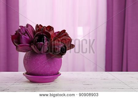 Beautiful tulips in pot on fabric background