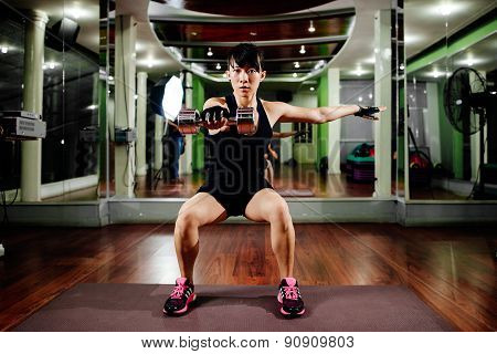 Asian Sexy Fitness Girl Instructor With Dumbbell Knee Bend