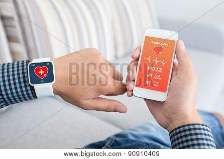 Male Holding Phone And Smart Watch With App Health Sensor