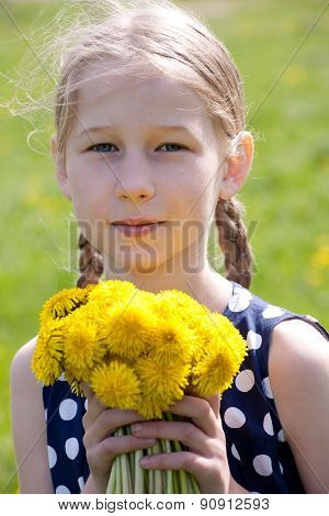 Young Girl With A Bunch Of Yellow Dandelions