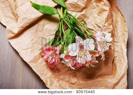 Beautiful Alstroemeria on parchment on wooden table, top view