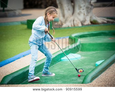 little girl playing golf outdoors