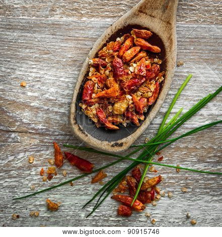 Dried chili pepper in a wooden spoon on a textured background