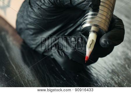 Tattoo artist at work close up