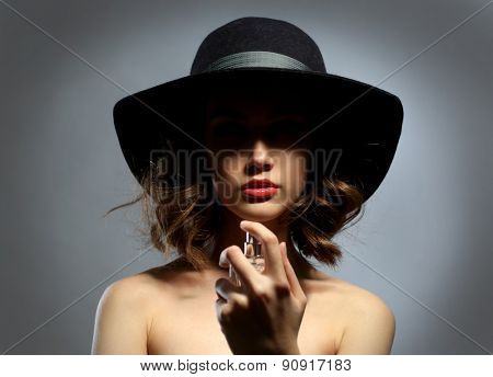 Beautiful woman with perfume bottle on gray background