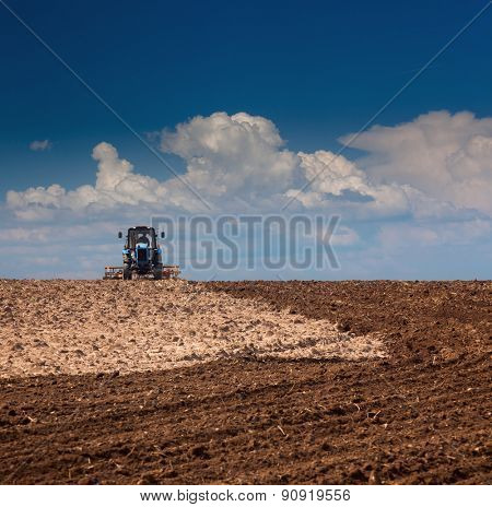 Agricultural Landscape - Tractor working on the field - sunny day