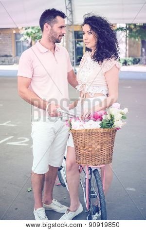 Couple with pink vintage bicycle in the summer park