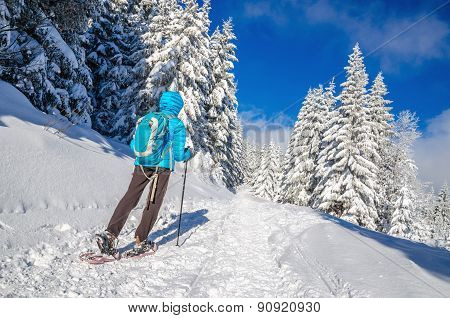 Young woman in dawn jacket hiking on snow shoes