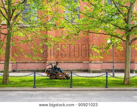 Public Servise: Man On A Mower Cutting Grass In The City