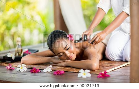 Young Asian woman enjoying a hot stone massage