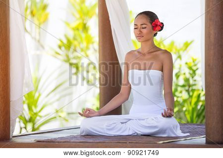 Beautiful young woman meditating with eyes closed