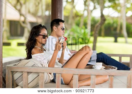 Couple sitting in big sunbed and enjoying in summer morning