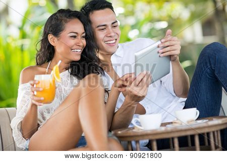 Laughing couple looking at tablet, summer vacation