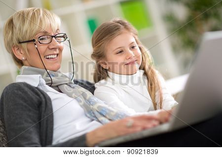 modern grandmother teaching grandchild how to use laptop computer at home