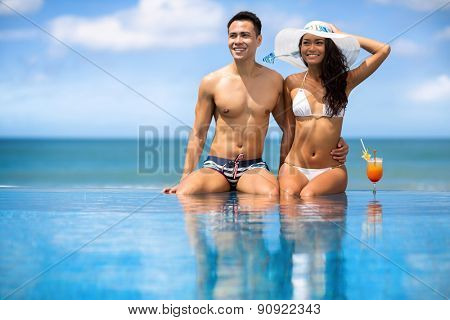 Beach couple looking,  Asian young couple sitting in swimming pool under sunny summer sun, travel holidays concept