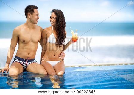 Cheerful Asian couple enjoying next swimming pool