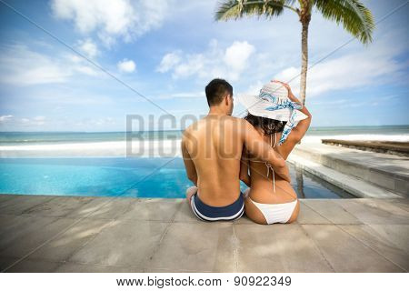 Attractive couple sitting next blue swimming pool