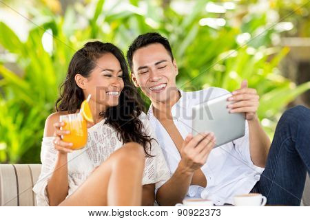 Balinese love couple with tablet pc on vacations