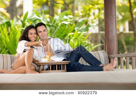 Young couple together comfort  sunbed in beautiful green resort