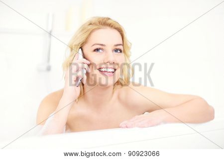 A picture of a happy woman talking on phone when taking a bath